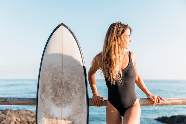 Attraktive frau mit dem surfbrett, das auf zaun sich lehnt