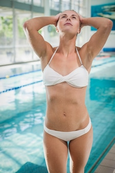Attraktive frau mit den händen auf ihrem kopf am pool