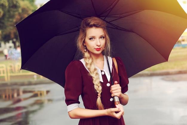 Attraktive frau mit einem schwarzen regenschirm aufwirft
