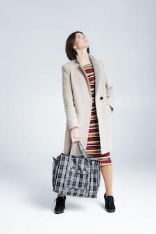 Attraktive frau mit einer großen einkaufstasche auf einem grauen hintergrund