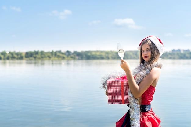 Attraktive frau mit geschenkbox und champagner