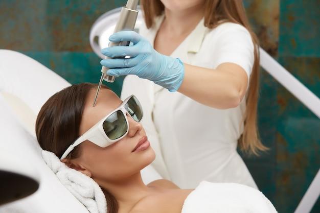 Attraktive frau mit gesichtsbehandlung mit laser im schönheitssalon durch professionelle kosmetikerin