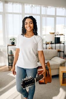 Attraktive frau mit gitarre wirft zu hause auf. hübsche dame mit musikinstrument entspannen sich im zimmer, weibliche musikliebhaberin ruht sich aus?
