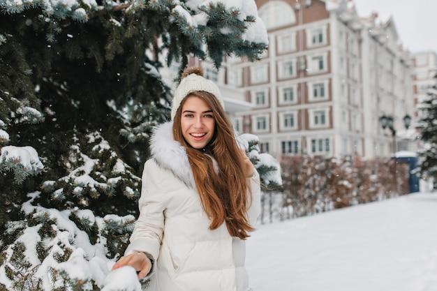 Attraktive frau mit glattem braunem haar, das mit selbstbewusstem lächeln nahe grüner fichte im winter aufwirft. atemberaubende junge dame trägt weißen mantel und lustigen hut, der spaß mit schnee hat.