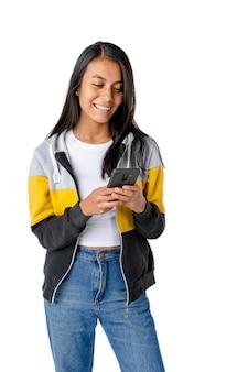 Attraktive frau mit glattem haar, die nachrichten auf einem handy oder smartphone auf einem reinen weißen hintergrund überprüft.