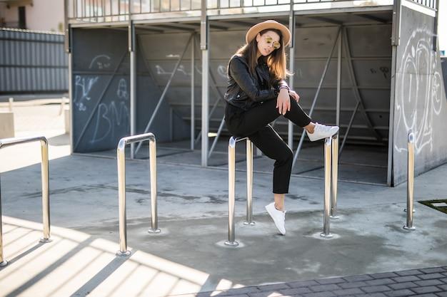 Attraktive frau mit goldhaar, die am skatepark im stadtzentrum aufwirft