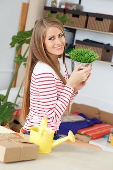 Attraktive frau mit gras mit gießkanne