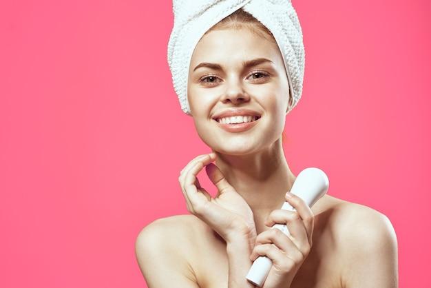 Attraktive frau mit handtuch auf kopfgesichtsmassage entspannung rosa