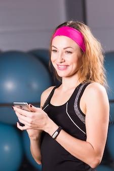Attraktive frau mit handy und fitness-tracker im fitnessstudio.
