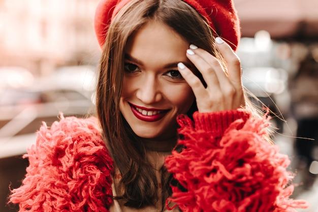 Attraktive frau mit hellen lippen, die lächeln und ihr dunkles haar berühren. nahaufnahmeporträt der dame im roten outfit und im kopfschmuck.