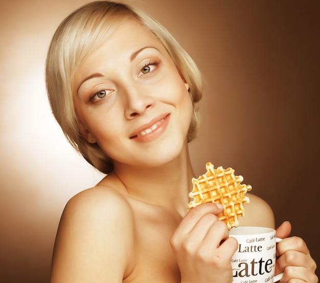 Attraktive frau mit kaffee und keksen