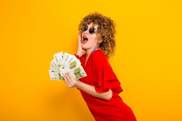 Attraktive frau mit kurzen lockigen haaren mit bargeld