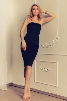 Attraktive frau mit langen blonden haaren im modischen schwarzen midikleid mit kurzen. lachendes weibliches modell, das gegen weiße wand auf hintergrund steht.