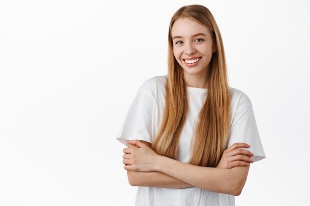 Attraktive frau mit langen glatten blonden haaren, verschränkten armen auf der brust, selbstbewusst und entschlossen, glücklich lächelnd, im t-shirt gegen weiße wand stehend
