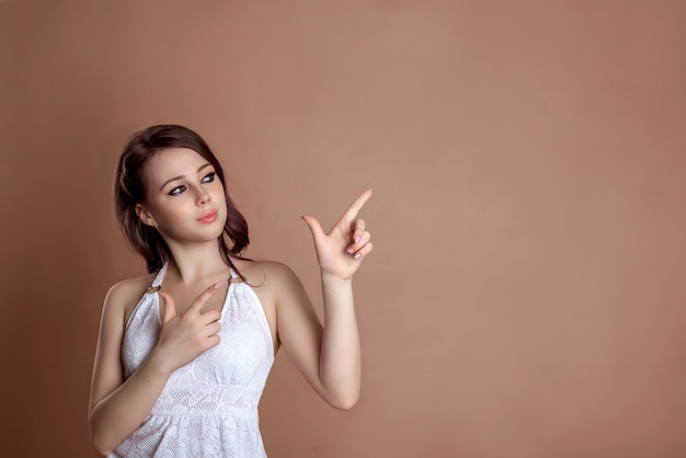 Attraktive frau mit lila volosami seitlich stehend auf die rechte seite des rahmens mit dem zeigefinger in richtung leerer copyspace, isoliert auf einem braun