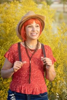 Attraktive frau mit mit rotem hemd und einem rucksack gehend auf die natur