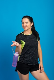 Attraktive frau mit muskulösem körper, der flasche des erfrischenden wassers hält. gesundheitskonzeption
