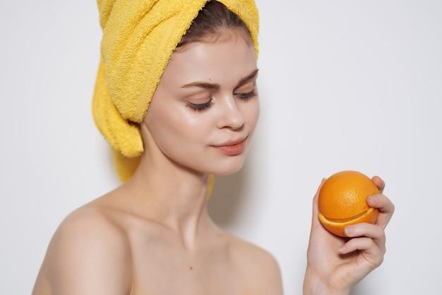 Attraktive frau mit nackten schultern orangen in den händen klare haut. foto in hoher qualität