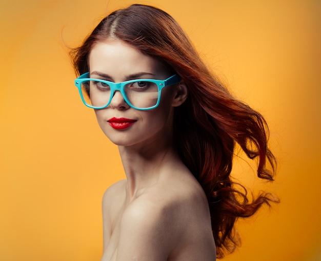 Attraktive frau mit nackten schultern rote lippen blaue brille nahaufnahme