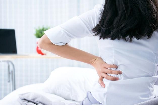 Attraktive frau mit rückenschmerzen zu hause im schlafzimmer