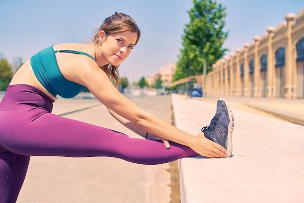Attraktive frau mit schönen blauen augen, die ihr bein streckt, während sie an einem sommermorgen in einem stadtpark glücklich aussieht