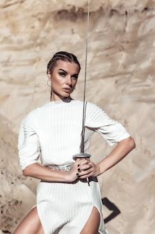 Attraktive frau mit schwert im weißen outfit. modeshooting in der wüste