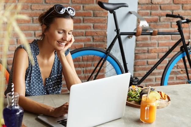 Attraktive frau mit sonnenbrille auf dem kopf, die einen videoanruf an ihren freund macht, schüchtern lächelt und sich mit dem ellbogen auf den tisch im café lehnt. nette weibliche nachrichtenfreunde online