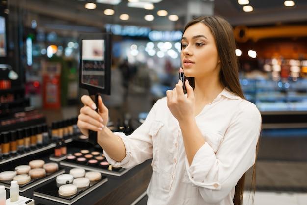 Attraktive frau mit spiegel trägt lippenstift im kosmetikgeschäft auf. käufer an der vitrine im luxus-beauty-shop-salon, kundin im modemarkt