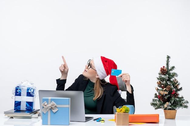 Attraktive frau mit weihnachtsmannhut und tragenden brillen, die an einem tischweihnachtsgeschenk sitzen und bankkarte halten, die oben im büro schaut