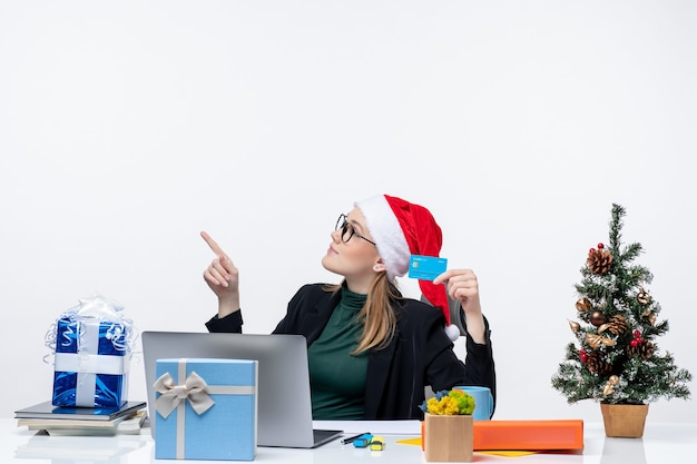 Attraktive frau mit weihnachtsmannhut und tragenden brillen, die an einem tischweihnachtsgeschenk sitzen und bankkarte im büromaterial halten