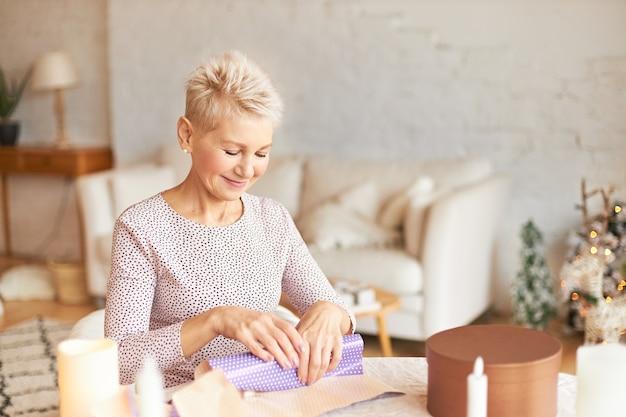 Attraktive frau mittleren alters mit blondem kurzhaarschnitt, der am tisch im wohnzimmer sitzt und weihnachtsgeschenk für ehemann in geschenkpapier einwickelt
