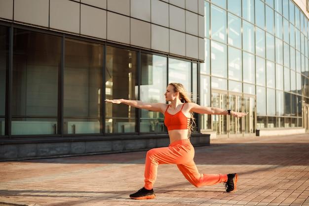 Attraktive frau praktiziert yoga und steht in der pose des kriegers zwei vor dem städtischen gebäude.