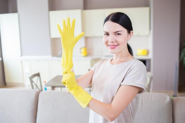 Attraktive frau schaut vor der kamera. sie steht im studio und zieht rechts einen gelben handschuh an. mädchen lächelt. sie sieht glücklich aus.