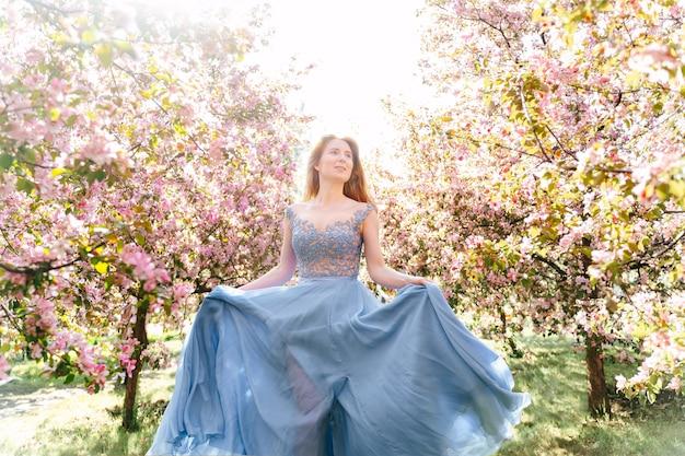 Attraktive frau spaziert im frühlingsrosapark und genießt die blühende natur in einem langen blauen kleid