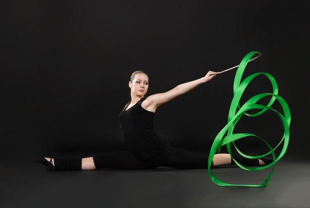 Attraktive frau tanzt mit grünem band vor dunklem hintergrund