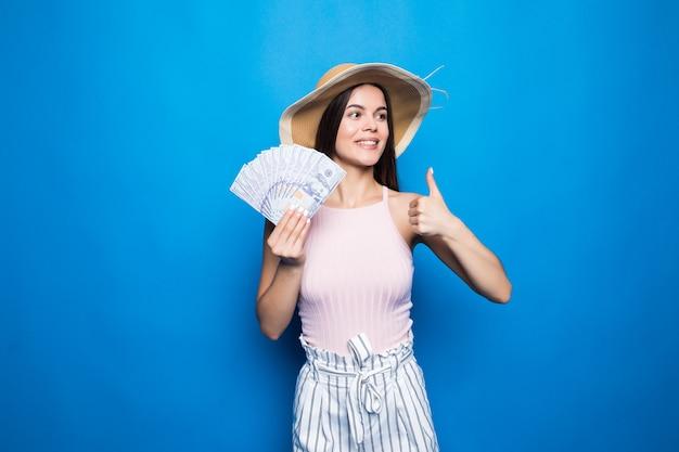 Attraktive frau tragen im strohhut, der banknoten von 100 usd zeigt, daumen hoch, lokalisiert über blauer wand.