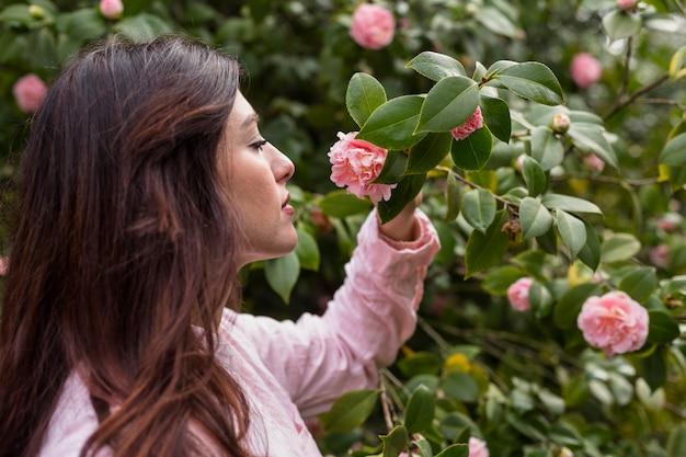 Attraktive frau, welche die rosa blume wächst auf grünem zweig hält