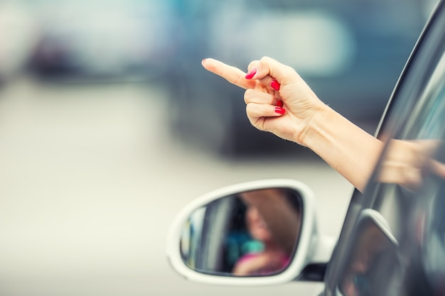 Attraktive frau zeigt obszöne geste von einem auto.