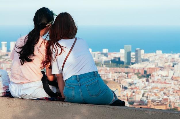 Attraktive frauen, die die skyline von barcelona beobachten und auf dem hügel des alten bunkers sitzen. draufsicht auf stadtstraßen und hafen. katalonien, spanien. viel spaß beim reisen konzept