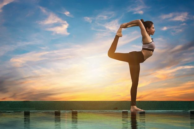 Attraktive frauen spielen yoga. am pool für ihre gesundheit