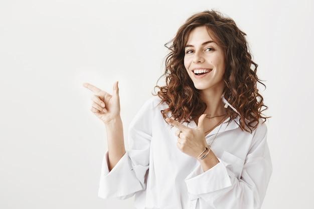 Attraktive freche frau, die finger nach links zeigt