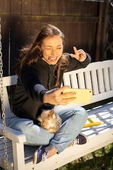 Attraktive freudige brünette frau mit langen haaren im schwarzen kapuzenpulli emotional macht v-geste selfies auf weißer schaukelbank mit yorkshire-hund emotional