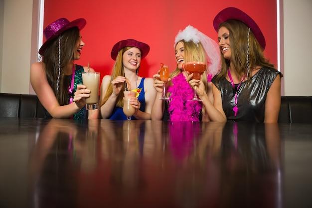 Attraktive freunde bei einer henne nacht trinken cocktails