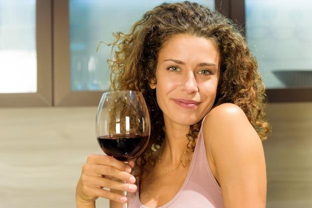 Attraktive freundliche junge frau mit einem schönen warmen lächeln, das mit einem großen eleganten glas rotwein anstößt, um in einem nahaufnahmeporträt zu feiern