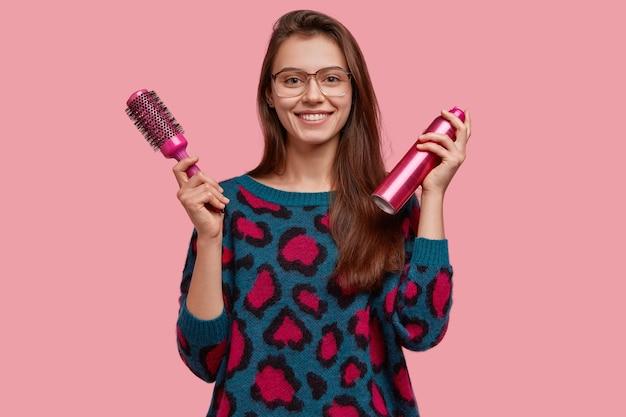 Attraktive friseurin hält kamm und haarspray, trägt große brille und pullover