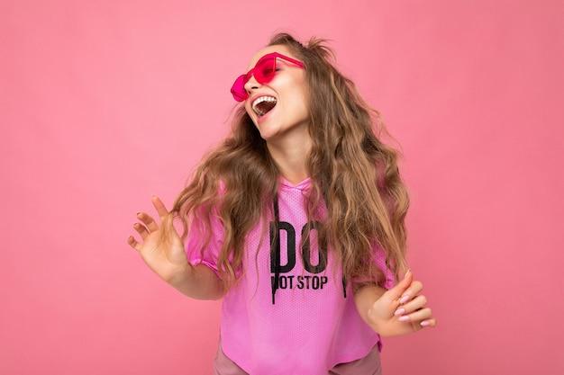 Attraktive fröhliche, glückliche junge blonde frau, die alltägliche stilvolle kleidung und moderne sonnenbrillen trägt, die auf einer bunten hintergrundwand isoliert sind und zur seite schauen