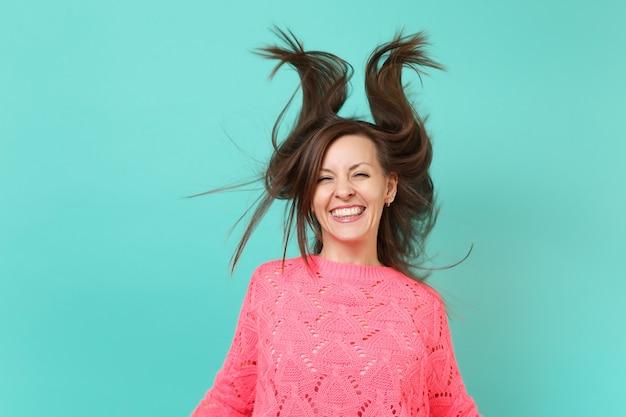 Attraktive fröhliche junge frau in gestricktem rosa pullover mit flatternden haaren einzeln auf blauem türkisfarbenem wandhintergrund, studioporträt. menschen aufrichtige emotionen, lifestyle-konzept. kopieren sie platz.