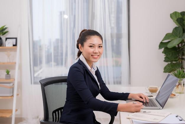Attraktive fröhliche junge geschäftsfrau, die am laptop arbeitet und lächelt, während sie an ihrem schreibtisch in einem hellen, modernen büro sitzt