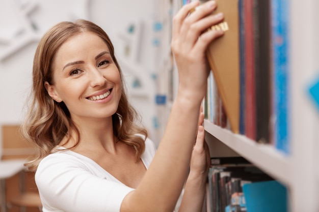 Attraktive fröhliche studentin, die lächelt, während sie ein buch auswählt, um an der bibliothek zu lesen