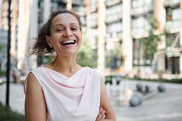Attraktive gemischtrassige hispanische, afroamerikanische frau, die mit einem zahnigen lächeln auf dem hintergrund der städtischen gebäude lächelt. selbstbewusstes portrait einer schönen geschäftsfrau
